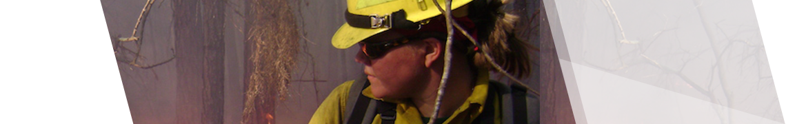 Female firefighter looking back at wildfire