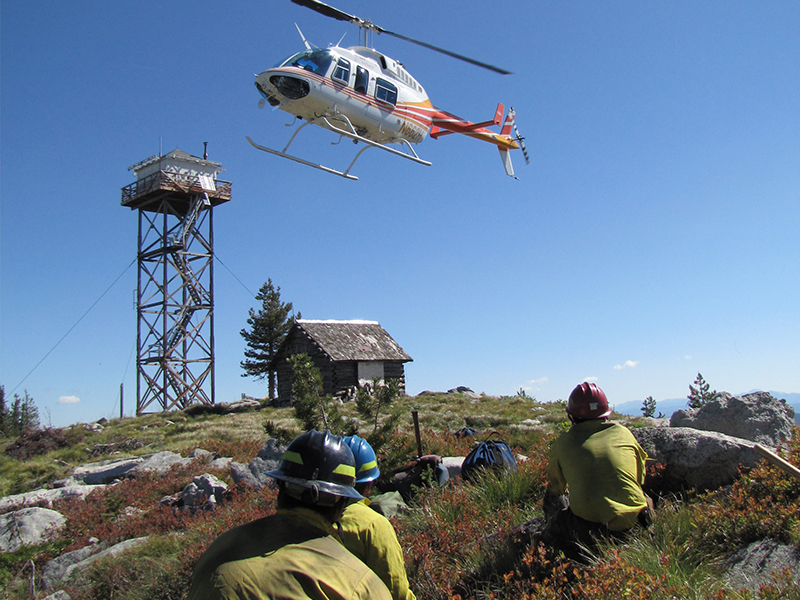 firefighters waiting for helicopter to land on mountain