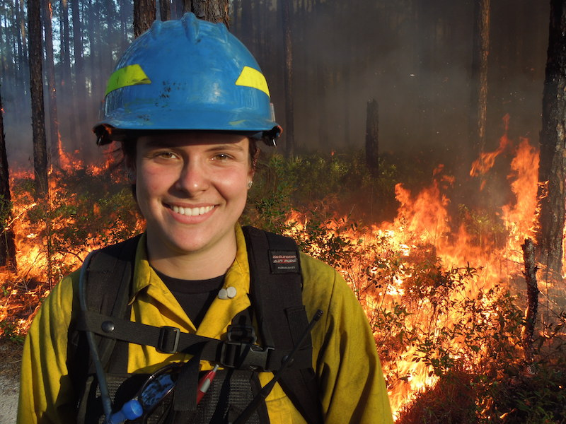 female firefighter smiling closeup, wildfire in background